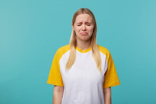 Ongelukkig jonge mooie blonde vrouw met casual kapsel houdt haar ogen gesloten terwijl ze helaas haar lippen nastreeft, staande op blauwe achtergrond met handen naar beneden