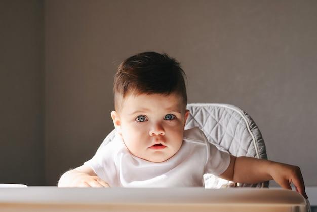Ongelukkig klein kind zittend op zijn stoel eten. verdrietig en ongelukkig kind op kleine stoel. boos peuterjongen vroeg in de ochtend
