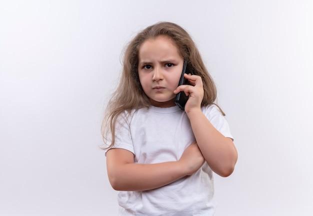 Ongelukkig klein schoolmeisje die witte t-shirtsprekers op telefoon op geïsoleerde witte muur dragen