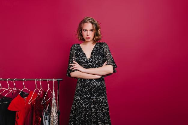 Ongelukkig meisje permanent op bordeaux achtergrond met armen gekruist in de buurt van hangers met jurken