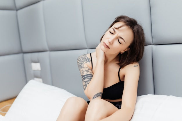 Ongelukkig moe jonge mooie vrouw hebben nekpijn wakker in de ochtend in haar bed