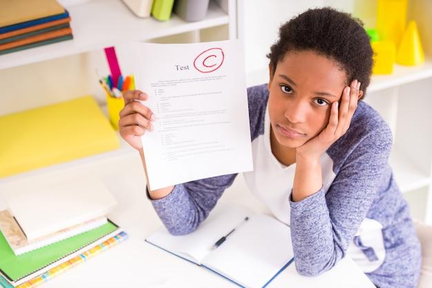 Ongelukkig mulat schoolmeisje aan tafel zitten.