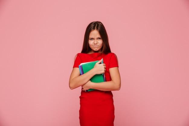 Ongelukkig ontevreden meisje in rode jurk bedrijf boek en kijken