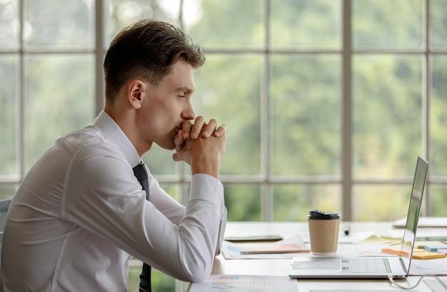 Ongelukkig overstuur gestresst depressief blanke zakenman zittend hand in hand op het hoofd met hoofdpijn. werknemer moe uitgeput omdat overwerk. mannelijke stafofficier versleten door overwerk.