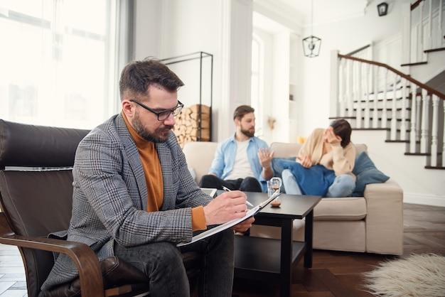 Ongelukkig paar ruzie, ruzie, onenigheid op het kantoor van psychologen, gefrustreerd jong gezin bespreken relatieproblemen met hun therapeut