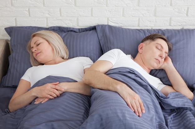 Ongelukkig paar van middelbare leeftijd in de slaapkamer thuis.