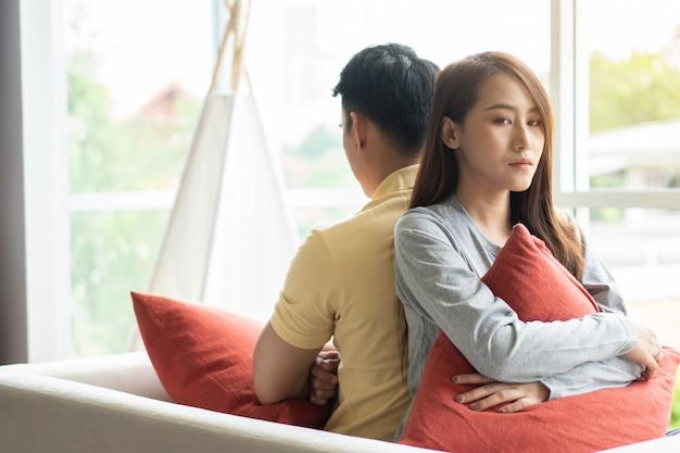 Ongelukkig stel zit achter elkaar op de bank en vermijd praten of kijken naar elkaar