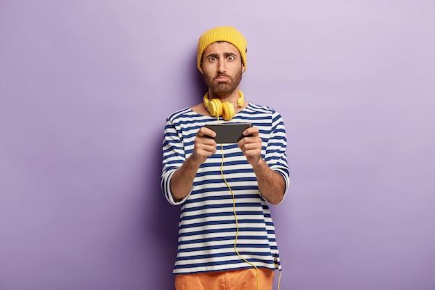 Ongelukkig stijlvolle man poseren met zijn telefoon