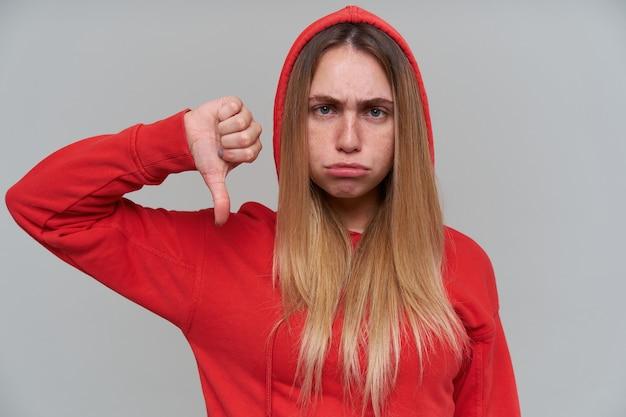 Ongelukkig teleurgestelde blonde jonge vrouw in rode hoodie die duimen naar beneden toont en camera over grijze muur bekijkt