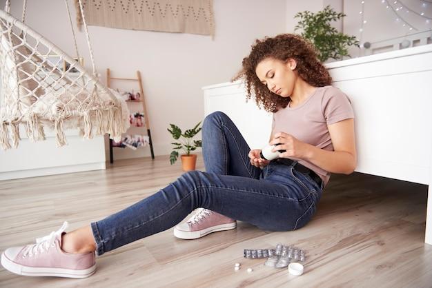 Ongelukkig tienermeisje dat veel pillen slikt