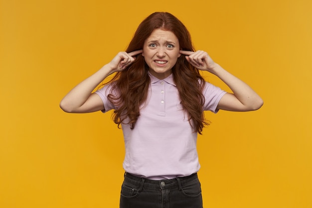 Ongelukkig uitziend meisje, ontevreden roodharige vrouw met lang haar. roze t-shirt dragen. sluit de oren met de vingers, geïrriteerd door lawaai. geïsoleerd over oranje muur