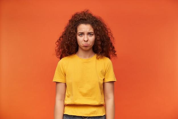 Ongelukkig uitziende vrouw met gember krullend haar gele t-shirt dragen