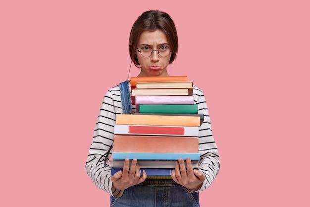 Ongelukkig verdrietig meisje ponkt onderlip, houdt enorme stapel boeken vast, voelt zich moe van het studeren en veel leren voor de sessie
