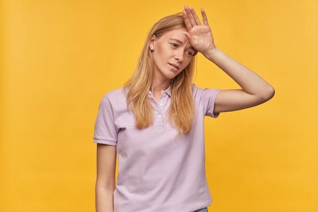 Ongelukkig vermoeide vrouw met sproeten in lavendel tshirt aanraken van haar voorhoofd met hoofdpijn en voelt zich ziek op geel