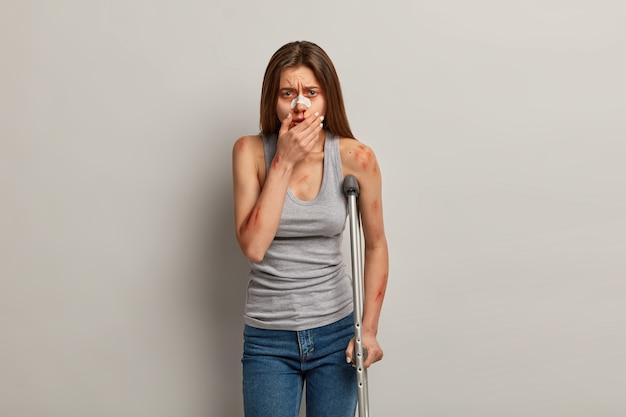 Ongelukkig vrouwelijk slachtoffer heeft bloedneus en verschillende krassen op lichaam na vreselijk verkeersongeval, heeft botbreuken, gebruikt krukken om te bewegen, kijkt wanhopig, geïsoleerd op grijze muur