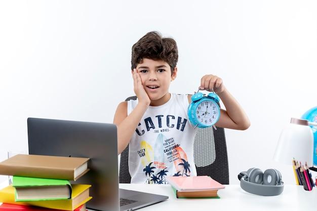 Ongelukkig weinig schooljongen zittend aan een bureau met schoolgereedschap wekker houden en hand op wang zetten geïsoleerd op een witte achtergrond