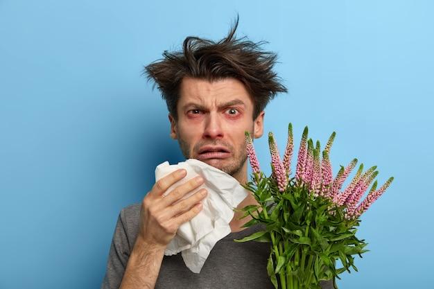 Ongelukkig zieke europese man lijdt aan rhinitis en allergie, niest in servet, heeft ademhalingsproblemen, houdt bloeiende plant vast, ziet er gefrustreerd uit, poseert over blauwe muur, voelt zich onwel