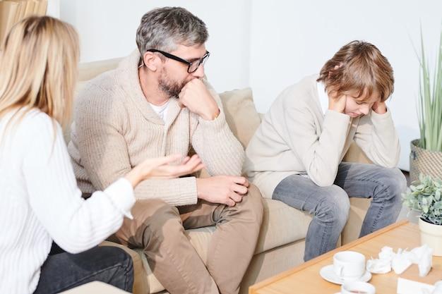 Ongelukkige adolescente jongen bij gezinstherapie