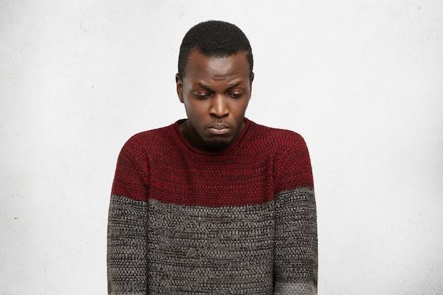 Ongelukkige afro-amerikaanse student die zich ongemakkelijk en beschaamd voelt, neerkijkt met droevige uitdrukking terwijl hij problemen heeft op de universiteit. portret van triest jonge zwarte man zonder motivatie en enegry