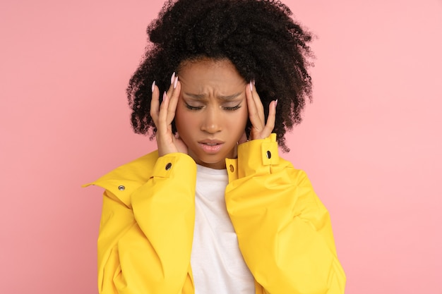 Ongelukkige afro-vrouw in gele regenjas lijdt aan hevige kloppende hoofdpijn bij het aanraken van haar slapen