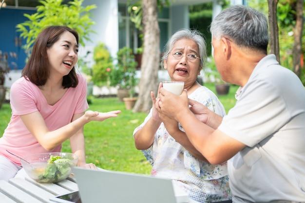 Ongelukkige aziatische senior vrouw anorexia en nee zeggen tegen maaltijden, ouderen wonen bij familie en zorgverleners proberen voedsel te voeren en oude vrouw geen eetlust, concept van gezondheidszorg en oudere zorgverleners