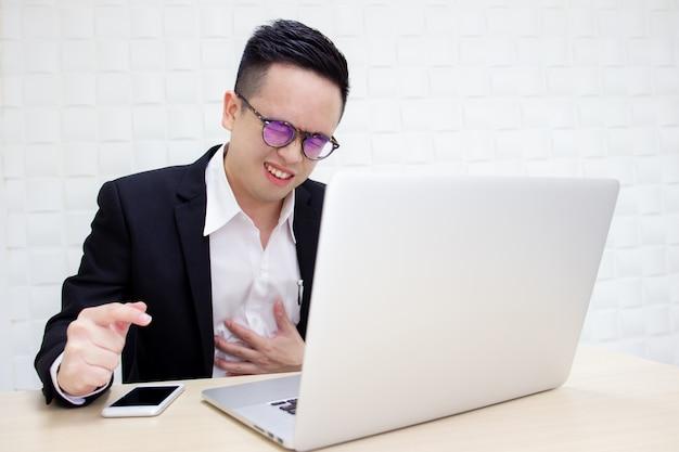 Ongelukkige aziatische zakenman die langdurig hard werkt.