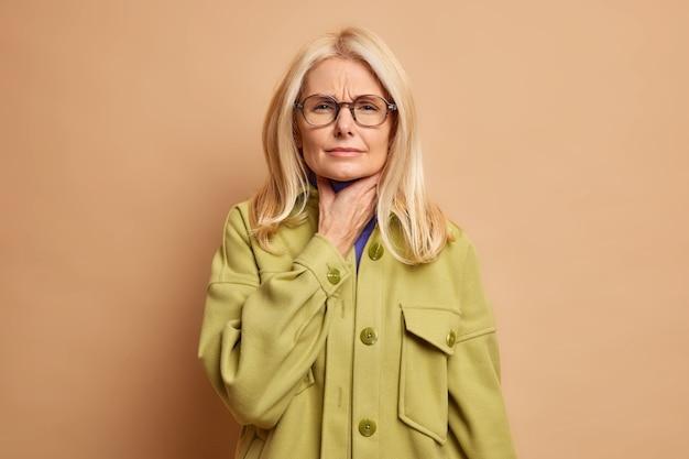 Ongelukkige bejaarde vrouw lijdt aan keelpijn, moeilijk te slikken, lijdt aan verstikking, voelt onaangename gevoelens