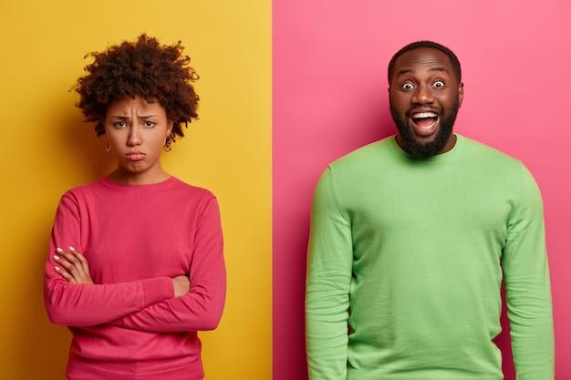 Ongelukkige beledigde vrouw staat met gekruiste armen, praat niet met echtgenoot. vrolijke bebaarde man heeft een donkere huid, giechelt positief om iets grappigs, drukt positieve emoties uit. mensen, reactie