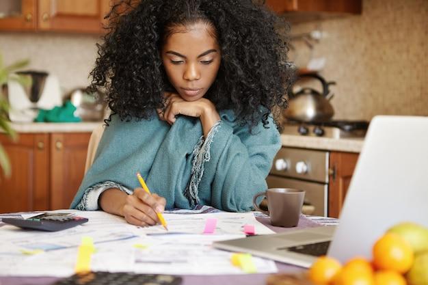 Ongelukkige depressieve jonge donkere huisvrouw die 's nachts alleen het binnenlandse budget beheert