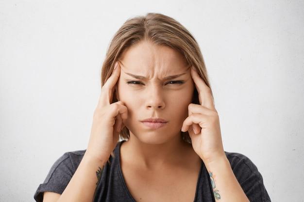 Ongelukkige depressieve vrouw die zich gestrest voelt, in haar slapen knijpt en de lippen nastreeft, met geconcentreerde gezichtsuitdrukking
