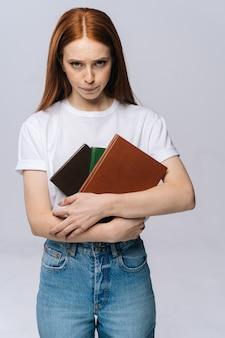 Ongelukkige, droevige jonge vrouw student die een boek vasthoudt en naar de camera kijkt op geïsoleerde achtergrond