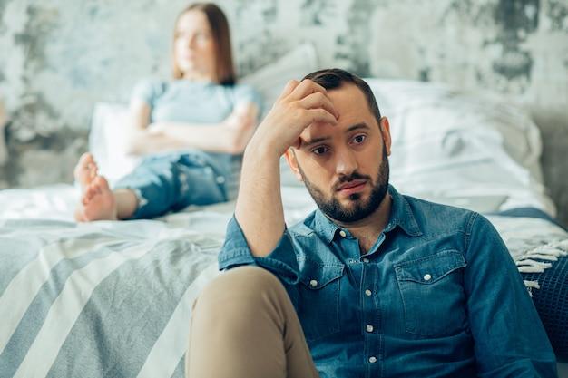 Ongelukkige echtgenoot die zijn voorhoofd aanraakt. beledigde vrouw zittend op de achtergrond met haar armen gekruist?