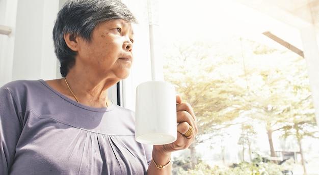 Ongelukkige eenzame aziatische hogere vrouw met een kop van koffie alleen thuis,