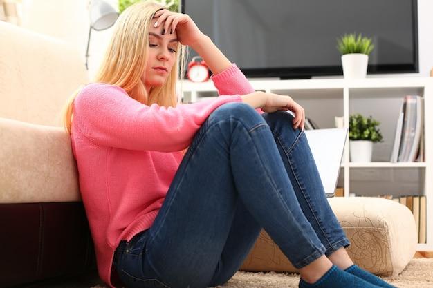 Ongelukkige eenzame depressieve vrouw thuis, ze zit op de bank, depressie concept