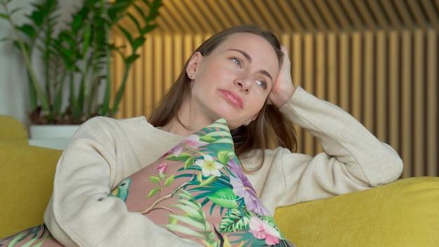 Ongelukkige eenzame depressieve vrouw thuis, ze zit op de gele bank