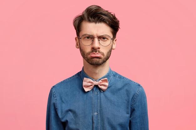 Ongelukkige ernstige ongeschoren jonge man met een norse uitdrukking, drukt antipathie uit, draagt een spijkerblouse met roze vlinderdas, houdt niet van iets. stijlvolle zakenman vertoont negatieve emoties na een mislukking