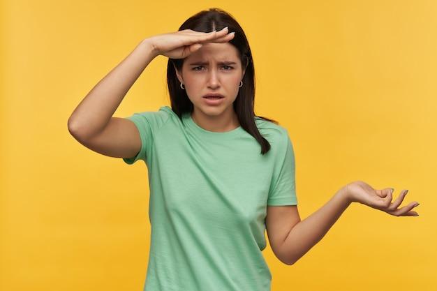 Ongelukkige geconcentreerde jonge vrouw met donker haar in mint tshirt die ver weg kijkt en copyspace op palm over gele muur houdt over