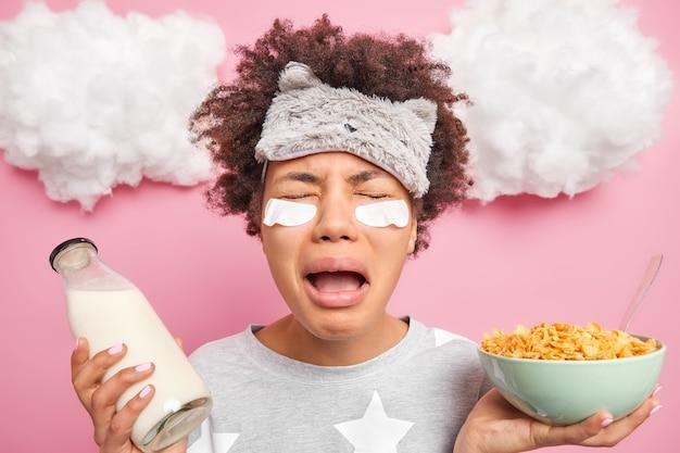 Ongelukkige gefrustreerde afro-amerikaanse vrouw huilt van wanhoop wakker in bed humeur wil niet naar bed houdt kom cornflakes en melk gaat ontbijten draagt pyjama
