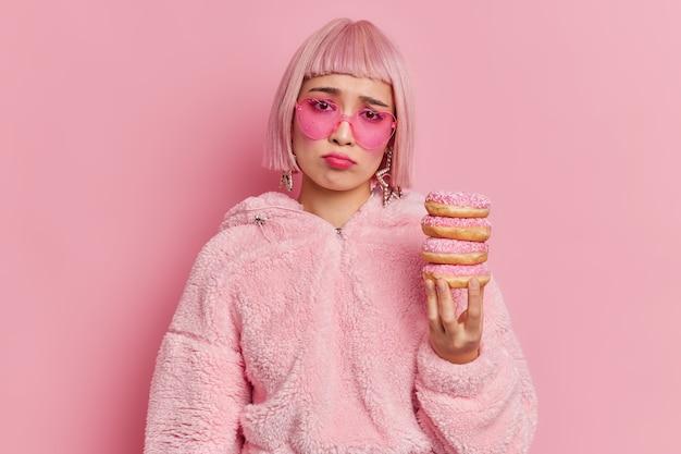 Ongelukkige gefrustreerde aziatische vrouw met bobkapsel houdt stapel heerlijke donuts vast, voelt zich verdrietig omdat ze moet eten, gekleed in bontjas en zonnebril