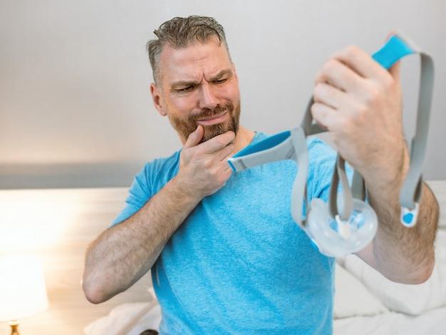 Ongelukkige geschokte man met chronische ademhalingsproblemen verrast door het gebruik van cpap-machine zittend op het bed