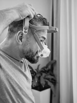 Ongelukkige geschokte man met chronische ademhalingsproblemen verrast door het gebruik van cpap-machine
