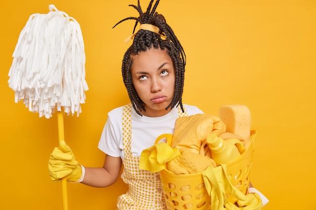 Ongelukkige huisvrouw voelt zich moe houdt dweil wasmand doet huishoudelijk werk