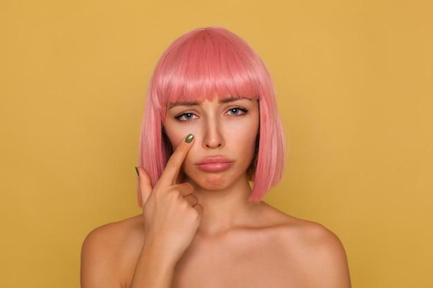 Ongelukkige jonge aantrekkelijke roze harige vrouw met bob kapsel dat haar lippen pruilt en droevig kijkt, wijsvinger onder haar oog houdt terwijl ze over mosterdmuur staat