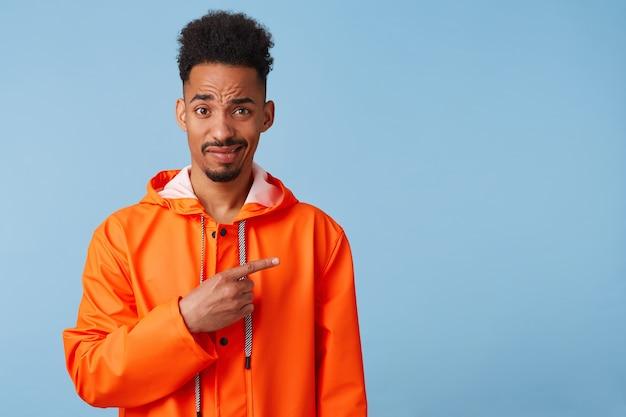 Ongelukkige jonge afro-amerikaanse man in oranje regenjas kijkt vragend uw aandacht wil trekken, wijst met de vingers naar de kopie ruimte aan de rechterkant. staat.