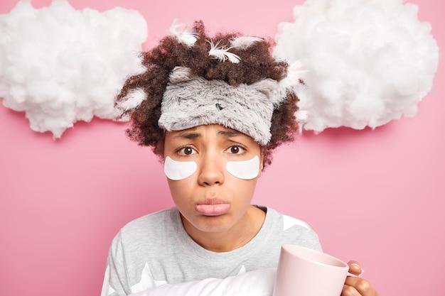 Ongelukkige jonge afro-amerikaanse vrouw kijkt droevig naar camera geldt patches slaapmasker pyjama drinkt koffie na aawakening geïsoleerd over roze muur witte wolken boven
