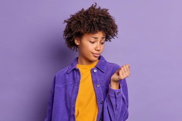 Ongelukkige jonge afro-amerikaanse vrouw kijkt naar haar nagels wil nieuwe manicure gekleed in stijlvolle kleding maken.