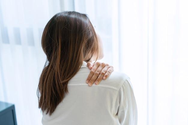 Ongelukkige jonge aziatische vrouw die aan schouderpijn op bed lijdt na 's ochtends wakker te worden