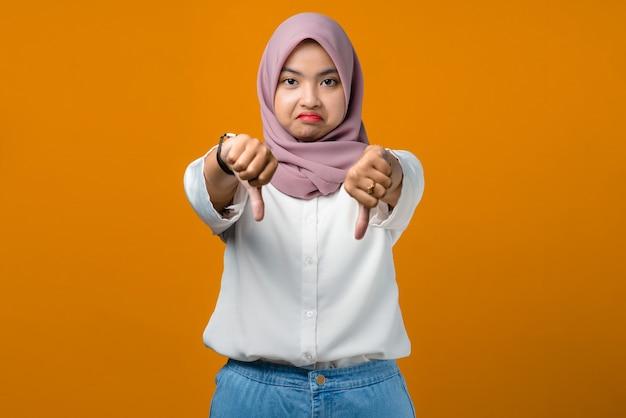 Ongelukkige jonge aziatische vrouw die duimen op geel geeft