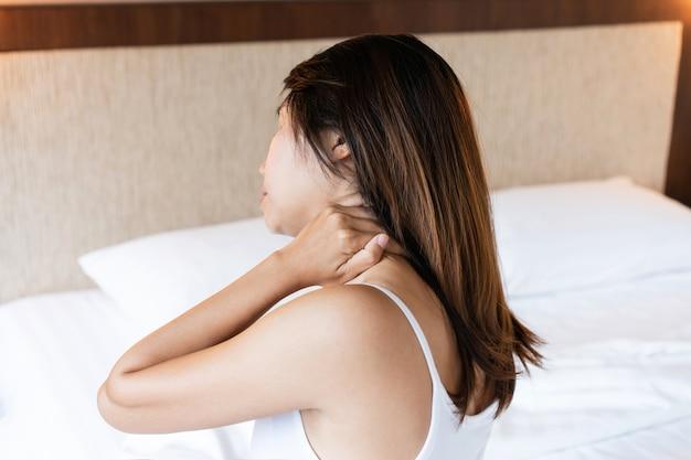 Ongelukkige jonge aziatische vrouw die lijdt aan nekpijn op bed na 's ochtends wakker te worden
