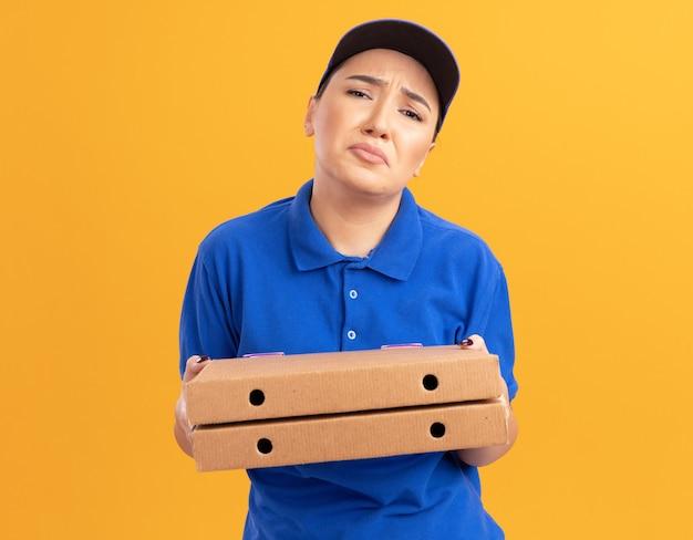 Ongelukkige jonge bezorger die in blauw uniform en pet pizzadozen houdt die voorzijde met droevige uitdrukking bekijken die zich over oranje muur bevindt